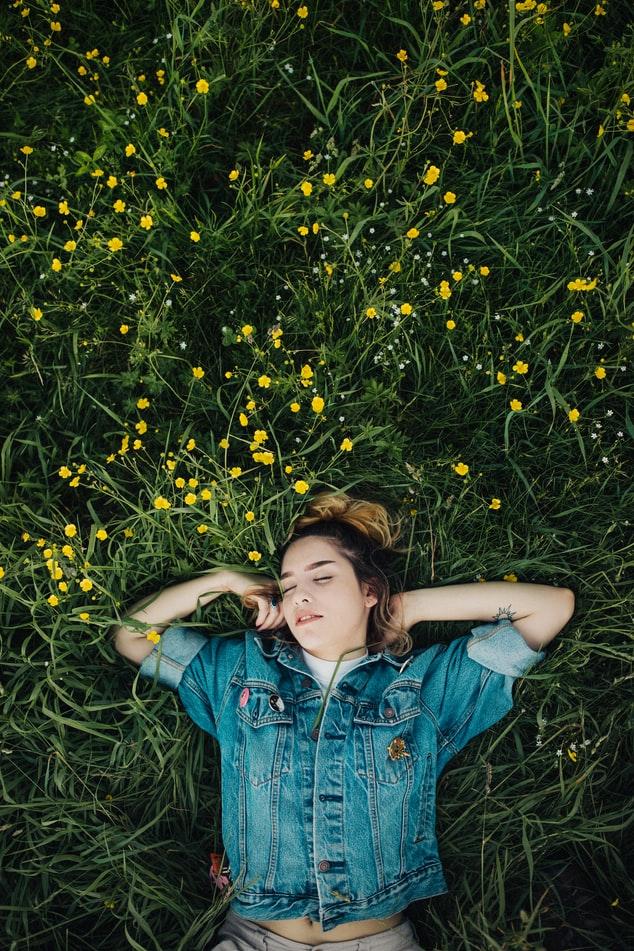 девушка в джинсовке лежит в желтых цветах