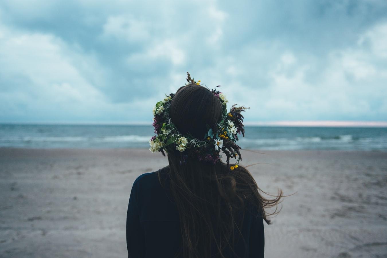 венок из цветов на голове брюнетки на берегу моря