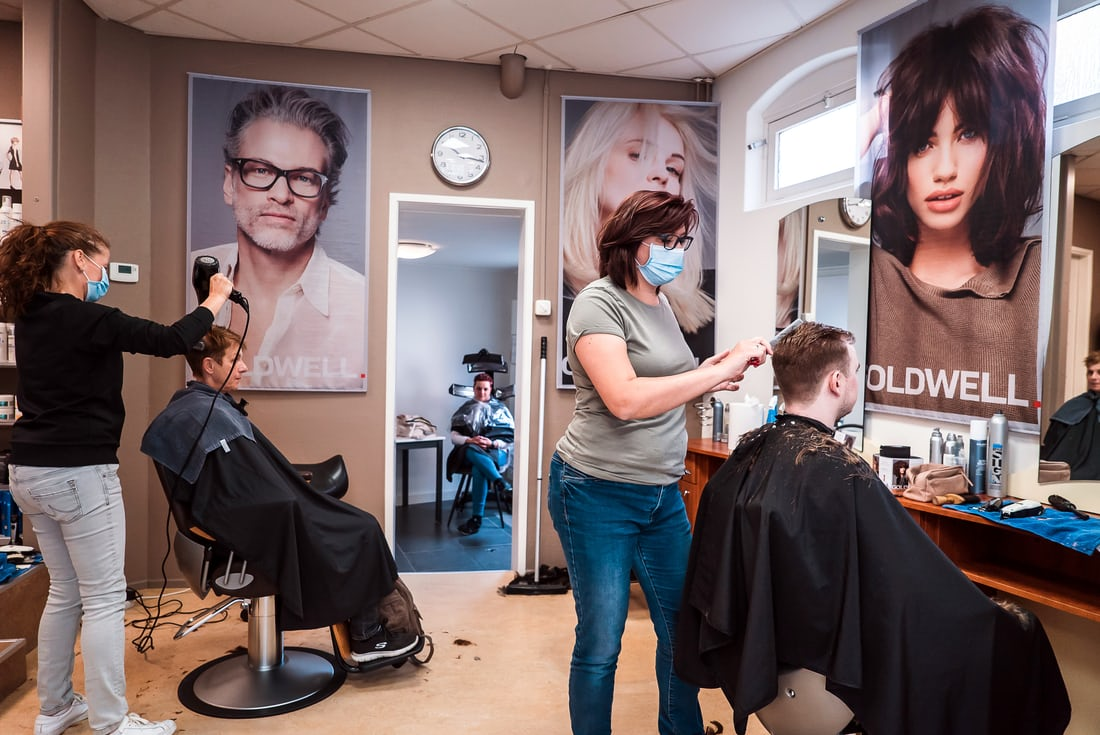 Парикмахеры в медицинских масках в салоне красоты