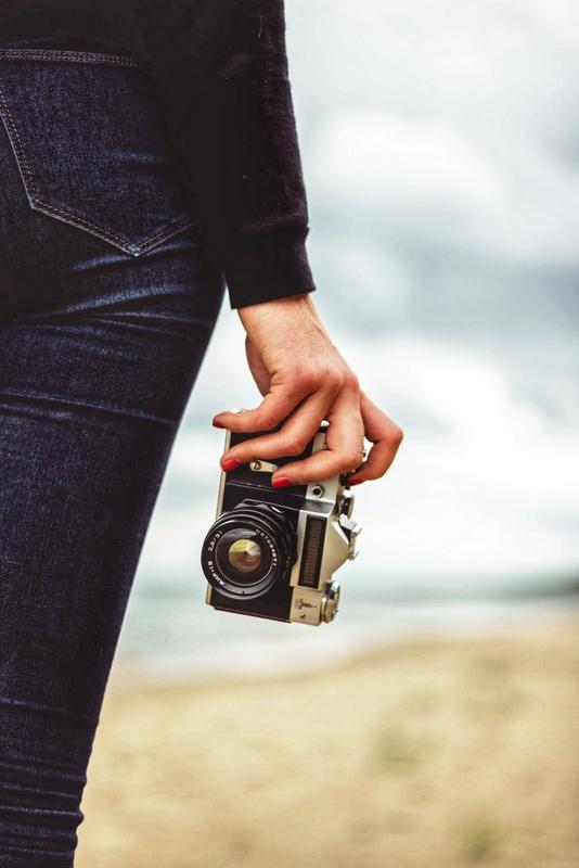 пленочный фотоаппарат в руке девушки